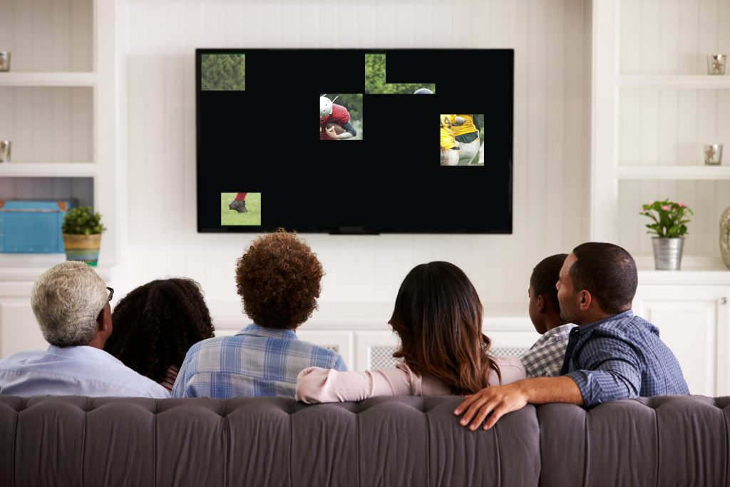 Men and Women sitting on couch watching a TV that is broken in places